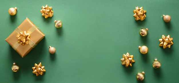 Bannière de noël avec cadeau doré et boules sur fond vert. vue de dessus. carte de voeux de noël ou du nouvel an avec espace de copie.