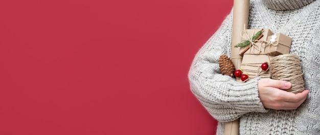 Bannière de noël lumineuse, rouge, espace de copie. une fille en pull tient des coffrets cadeaux, du papier kraft, une bobine avec une corde, un décor de noël. cadeaux faits à la main pour la nouvelle année.