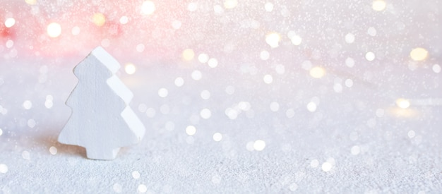 Bannière de noël - petit arbre en bois blanc sur fond abstrait de lumières de noël.