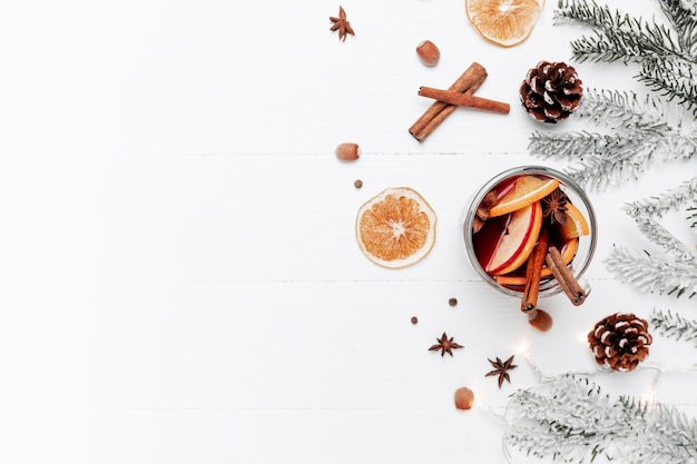 Bannière de noël à plat sur fond gris blanc avec une tasse en verre ou une tasse de vin alcoolisé chaud, décorations de noël, cannelle, orange, pomme, diverses épices, sapin, cône, anis. photo conceptuelle