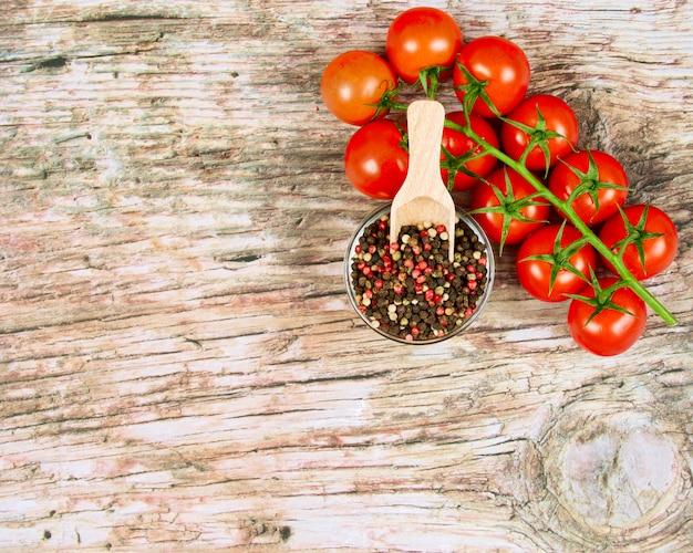 Bannière de nourriture horizontale avec des tomates cerises rouges mûres et des grains de poivre sur fond en bois.