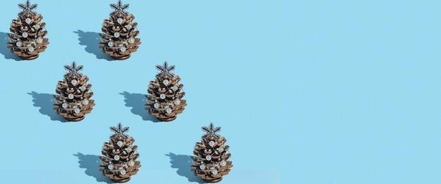 Bannière de nouvel an avec motif de nouvel arbre de noël alternatif fait de pommes de pin avec des perles sur un fond bleu avec une ombre dure