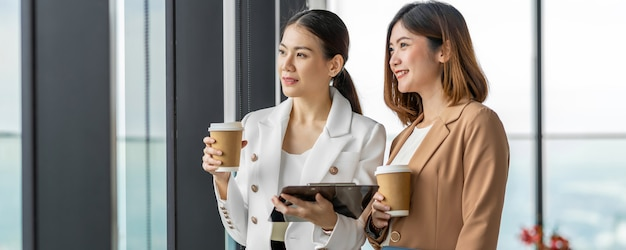 Bannière, page web ou modèle de couverture de deux femmes d'affaires asiatiques parlant pendant la pause-café dans un bureau moderne