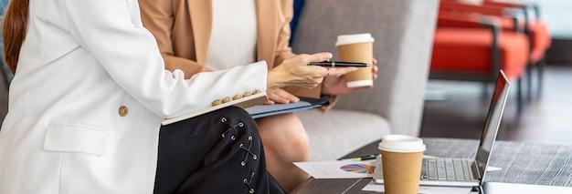 Bannière, page web ou modèle de couverture de deux femmes d'affaires asiatiques travaillant avec l'entreprise partenaire par stylo à ordinateur portable dans un bureau moderne ou un espace de coworking, concept de partenaire et collègue