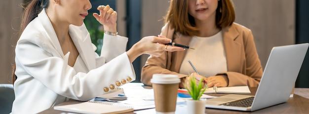 Bannière, page web ou modèle de couverture de deux femmes d'affaires asiatiques travaillant avec l'entreprise partenaire par stylo à ordinateur portable