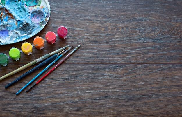 Bannière palette lumineuse peinture pinceaux sur fond en bois.