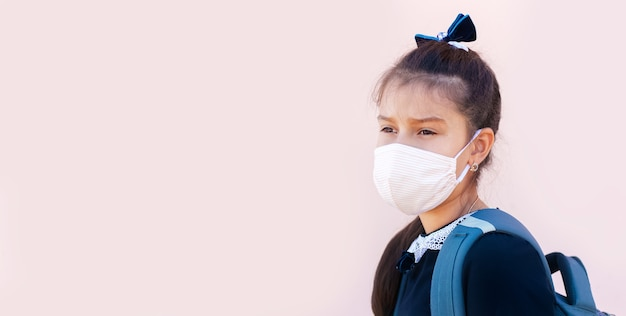 Bannière panoramique d'une écolière portant un masque médical, sur fond rose.