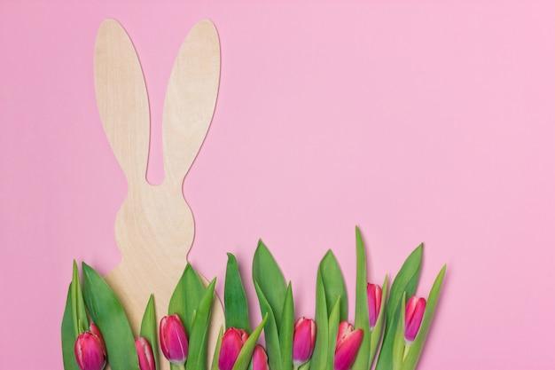 Bannière de pâques avec figure de lapin en bois et tulipes fraîches violettes. espace de copie pour le texte