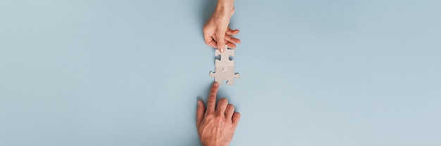 Bannière de partenaires commerciaux, homme d'affaires et femme d'affaires, joignant deux pièces de puzzle vierges assorties. vue de dessus