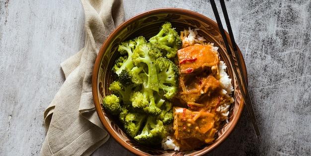 Bannière de plat de saumon thaï à la noix de coco avec du brocoli frais et du riz dans un bol en argile avec des baguettes