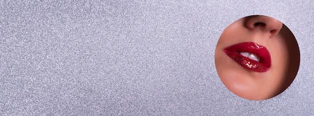 Bannière publicitaire de salon de beauté avec espace de copie. vue de lèvres brillantes avec des paillettes à travers le trou dans le fond de papier argenté.