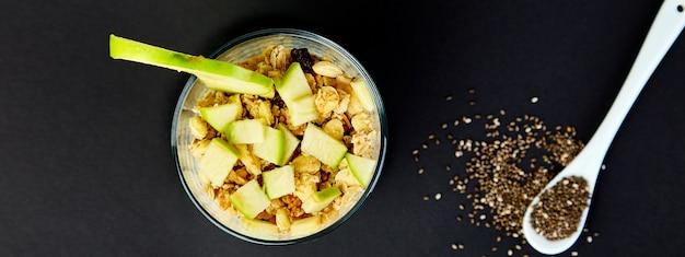 Bannière de pudding de chia sain avec des pommes et du granola en verre.