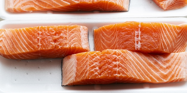 Bannière de saumon frais, coupé en morceaux et prêt pour la cuisson.