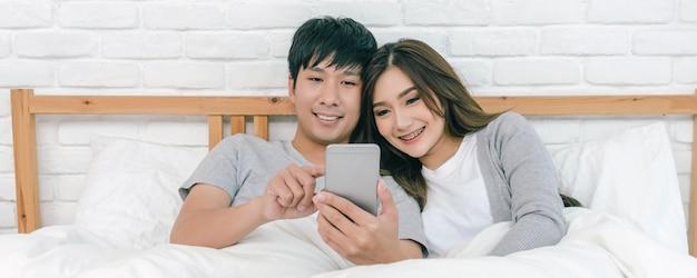 Bannière et scène de couverture de happy asian lover utilisant la technologie téléphone intelligent sur le lit dans la chambre à la maison, couple et style de vie, concept de petit ami et petite amie