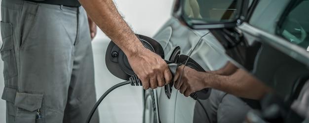 Bannière et scène de couverture de la main rapprochée du technicien chargeant l'électricité de la voiture en maintenance