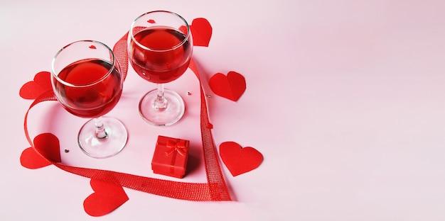 Bannière sur une surface claire deux verres de vin rouge, une boîte cadeau rouge avec des coeurs rouges et un ruban