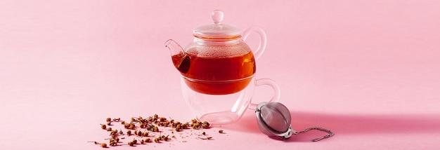 Bannière de thé dans une théière en verre sur fond rose et un filtre à infuseur en métal