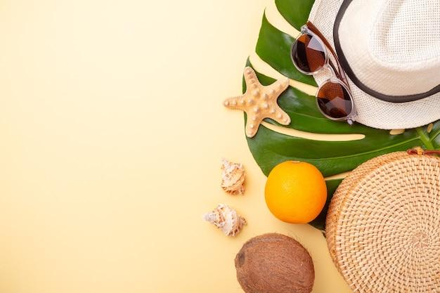 Bannière de vacances d'été. sac en rotin, lunettes de soleil, chapeau et fruits exotiques sur fond jaune.