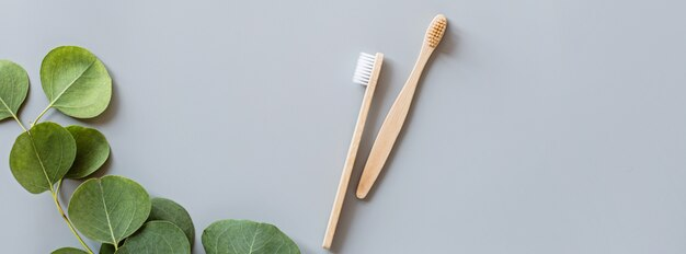 Bannière web avec des brosses à dents en bambou naturel eco plat poser sur fond gris