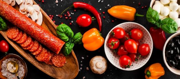Bannière web avec des ingrédients de pizza sur fond gris foncé. la saucisse pepperoni, le fromage mozzarella, les tomates, les olives, les champignons et la farine sont des produits différents pour faire des pizzas et des pâtes