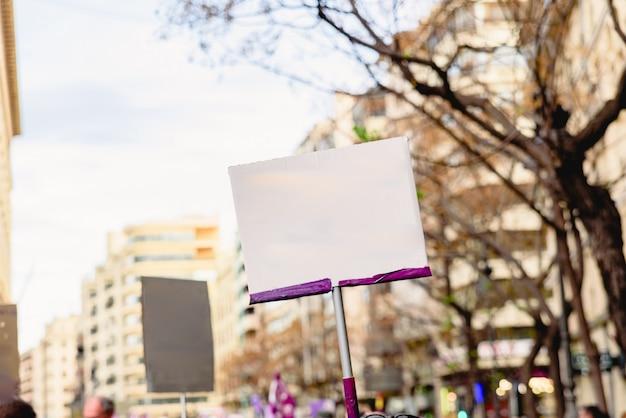 Bannières vierges tenues par des personnes lors de manifestations, à compléter avec du texte.