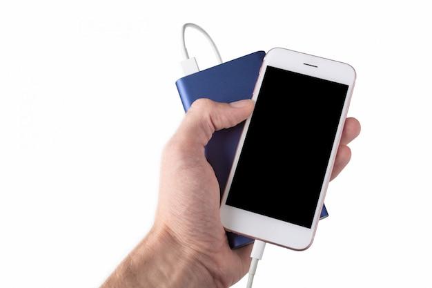 Banque alimentaire bleu avec un smartphone à la main sur un mur blanc isolé.