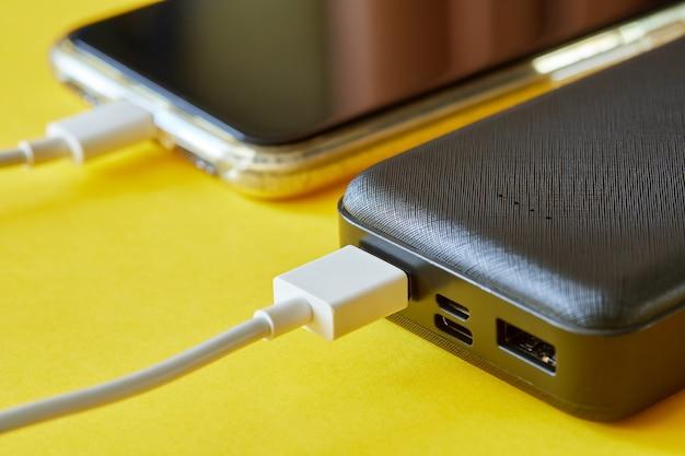 La banque d'alimentation charge le smartphone à l'aide d'un câble usb