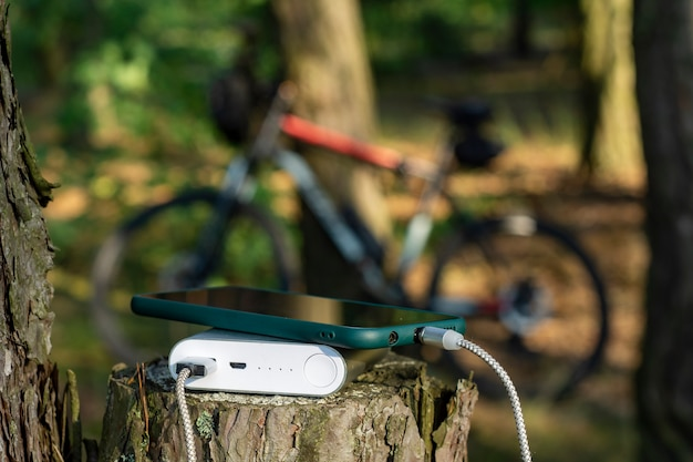 La banque d'alimentation charge un smartphone dans la forêt sur le fond d'un vélo.