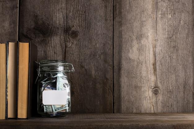 Banque avec de l'argent sur l'ancienne étagère en bois.