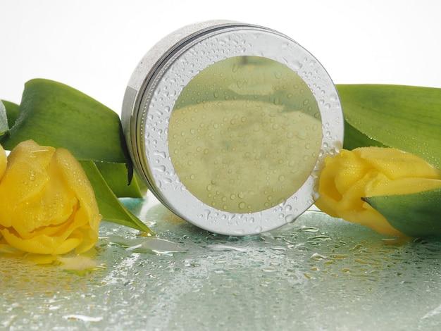 Banque de cosmétiques, gommage, avec des gouttes d'eau, près des tulipes. le concept de peau délicate et de rajeunissement.