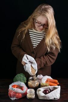 Banque de plastique réutilisable de remplissage femelle avec des grains de sac écologique sur table en bois.