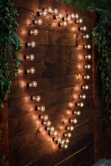 Banquet de mariage sur le fond du coeur des lampes dans la forêt parmi les arbres sur la piste verte