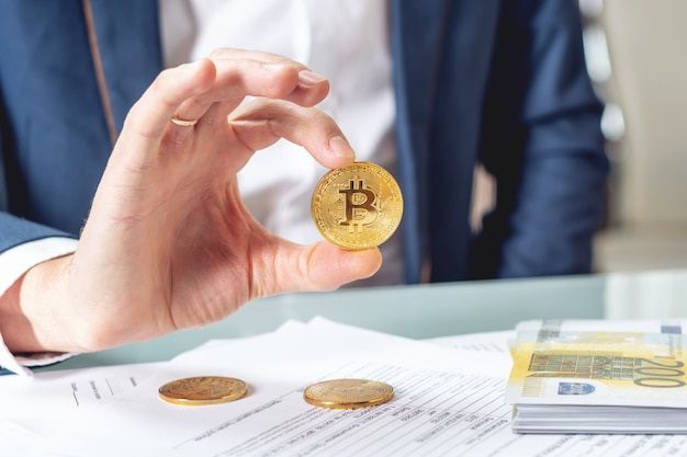 Banquier d'affaires assis à table avec des papiers tenant une pièce de monnaie bitcoin. echange et vente de crypto-monnaie