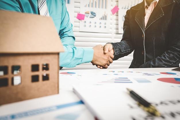 Banquier se serrant la main avec le client pour approuver la location d'une maison.
