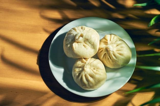 Baozi avec différentes garnitures (bœuf ou porc) dans une assiette blanche. recette et cuisine chinoise. pain de viande chinois cuit à la vapeur