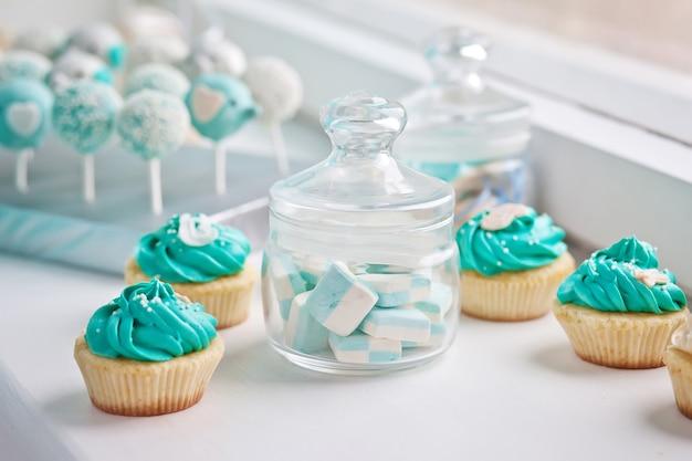 Bar à bonbons à l'anniversaire de guimauves dans un verre et petits gâteaux sur une surface en bois