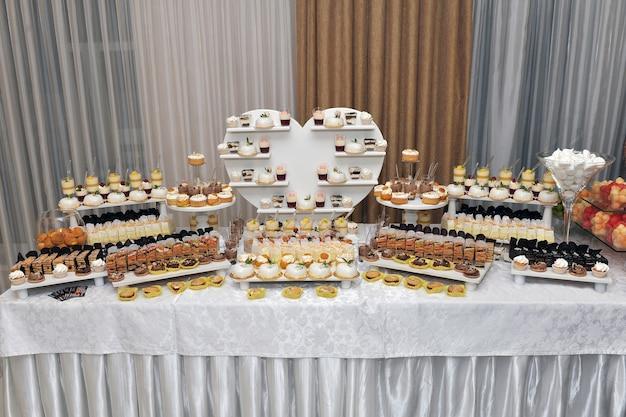 Bar à bonbons avec biscuits, cocktails et boissons pendant le mariage.