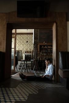 Bar fermé en raison du verrouillage de l'épidémie de pandémie, propriétaire stressé d'une petite entreprise parlant au téléphone, dépression. homme d'affaires épuisé, bouleversé.