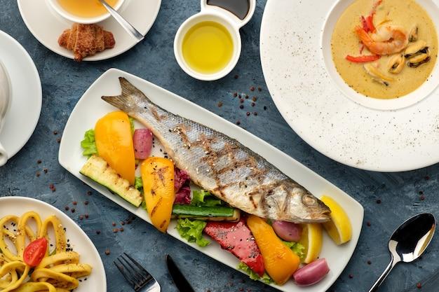 Bar grillé aux légumes, soupe de fruits de mer et calamars frits.