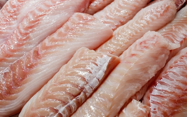 Bar, hamour, mérou, filet de bar de nombreux morceaux tranchés empilés en vrac dans le marché aux poissons.