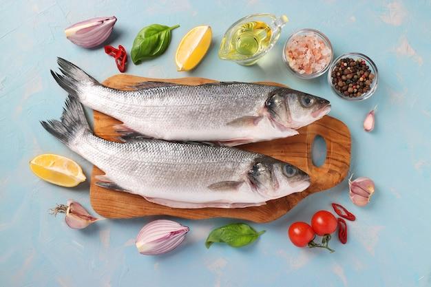 Bar de poisson cru avec des ingrédients et des assaisonnements comme le basilic, le citron, le sel, le poivre, les tomates cerises et l'ail sur une planche de bois sur une surface bleu clair. vue d'en-haut