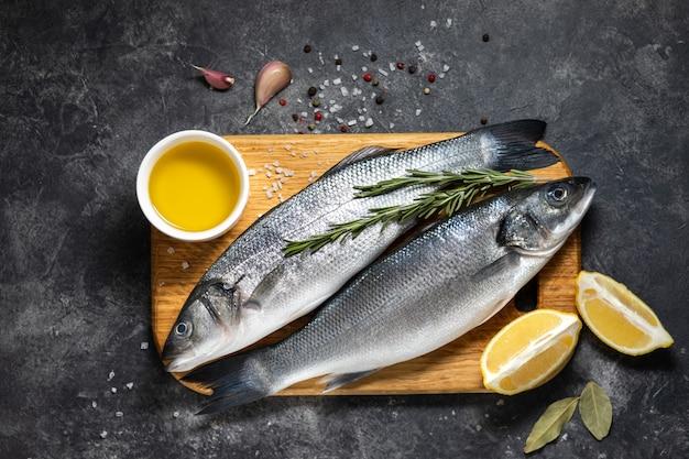 Bar de poisson frais et ingrédients pour la cuisine, citron et romarin
