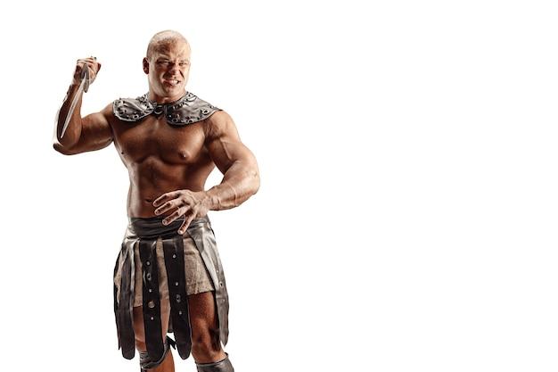 Barbare sévère en costume de cuir avec épée. portrait de gladiateur musclé chauve.