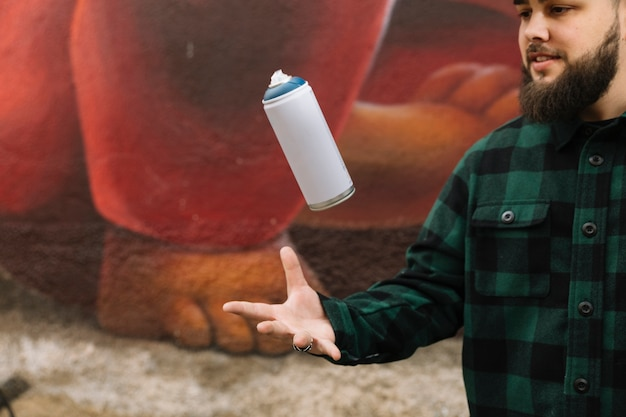 Barbe jeune homme jetant un flacon pulvérisateur dans l'air