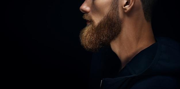 Barbe vue de côté en gros plan sur fond noir. célibataire debout dans le profil jeune bel homme barbu sérieux en sweat à capuche sombre. copiez l'espace libre sur la gauche