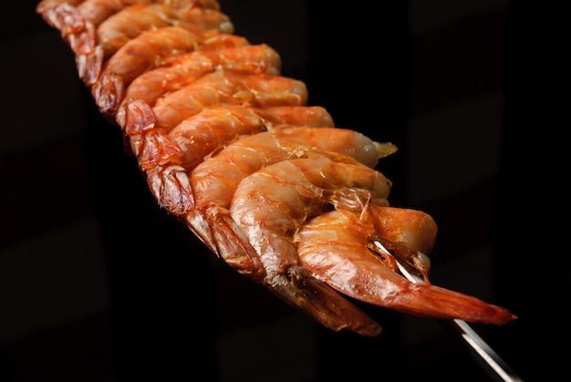 Barbecue de crevettes en brochettes sur fond noir gastronomie brésilienne
