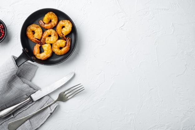 Barbecue de crevettes grillées style mixte épicé, sur une poêle à frire, sur blanc