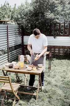 Barbecue dans la cour. mans mains grillant kebab et légumes sur des brochettes en métal.