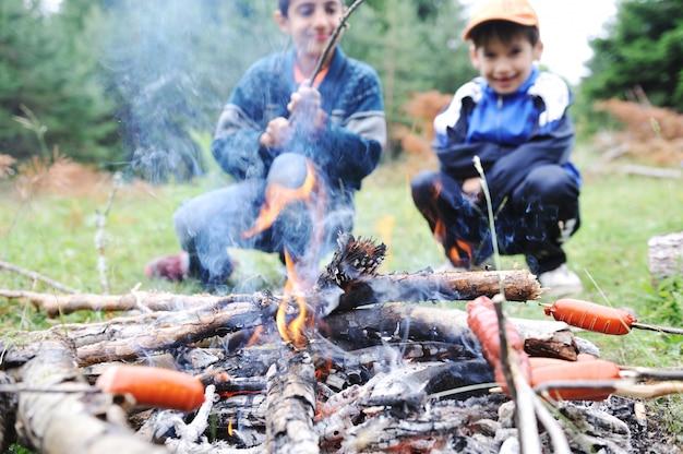Barbecue dans la nature, groupe de personnes préparant des saucisses sur le feu (note: dof peu profond)