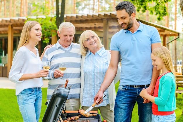 Barbecue familial. famille heureuse de cinq personnes faisant griller de la viande sur le gril dans la cour arrière de leur maison